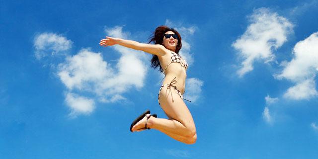 青空でジャンプする女性